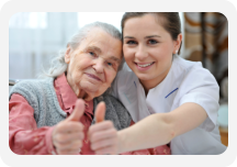 a nurse and an old woman showing their thumbs up